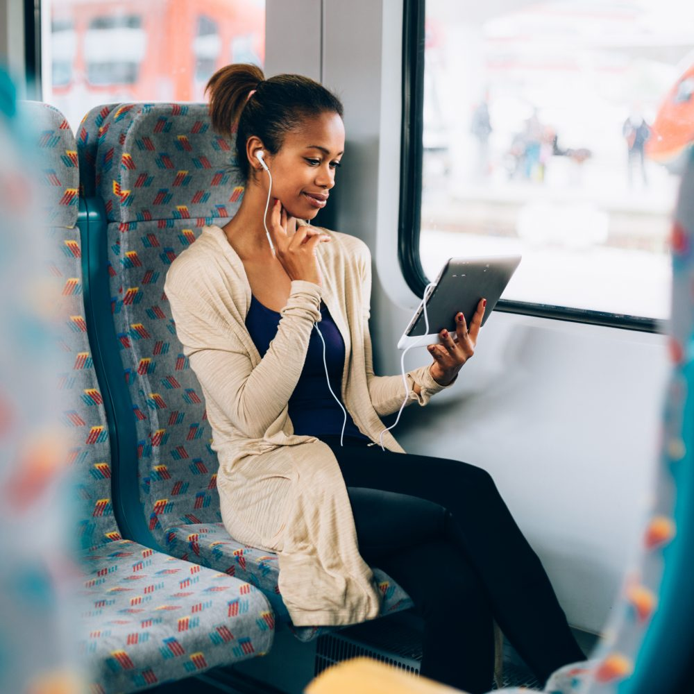 Young black woman listening to music on train using tablet compu