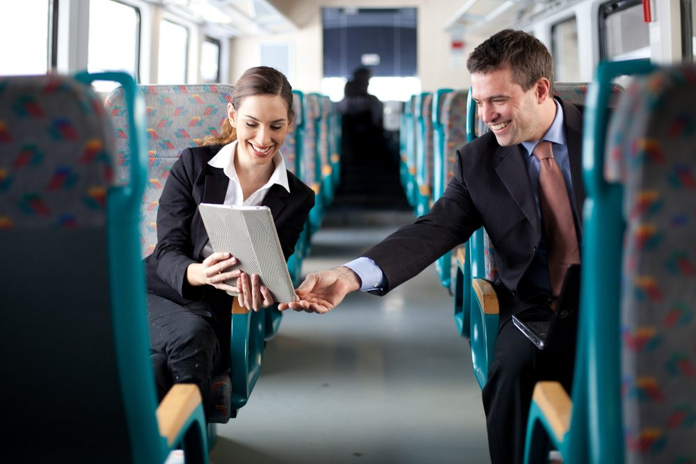 businesswoman-and-man-on-train-with-tablet