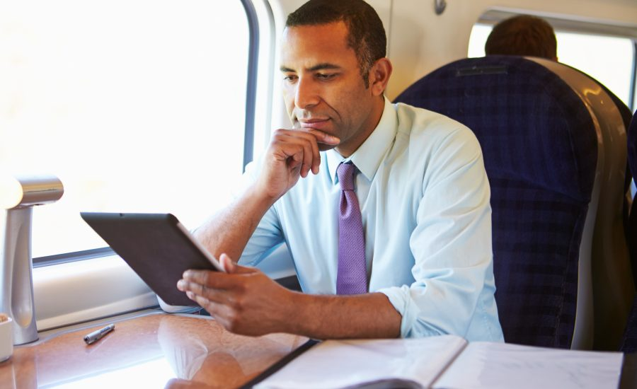Man holding a tablet on a train