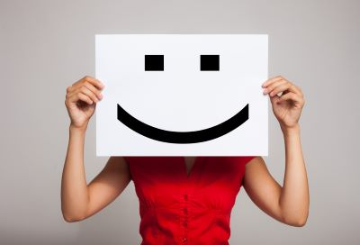 person holding smiling emoji print out over face