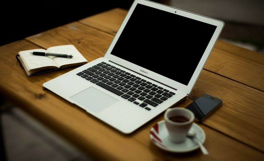 laptop on wooden desk with a notepad and coffee either side