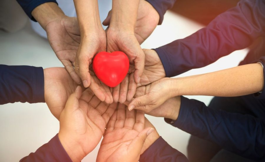 several hands holding a heart