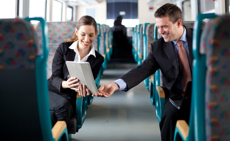 business woman showing notepad to business man on a bus