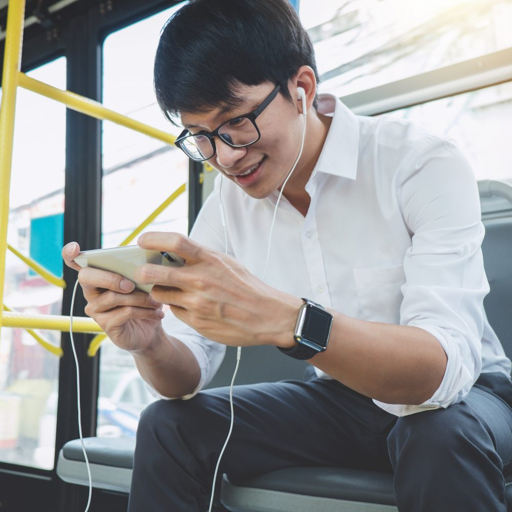 Young Man Sitting On A Bus Using Smartphone